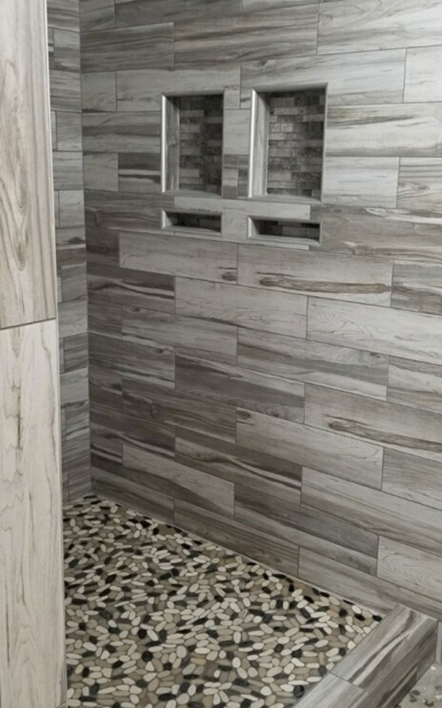 Big Bob's Flooring installed this custom shower with 6 x 24 tile coordinated with pebble mosaic accent on the floor.