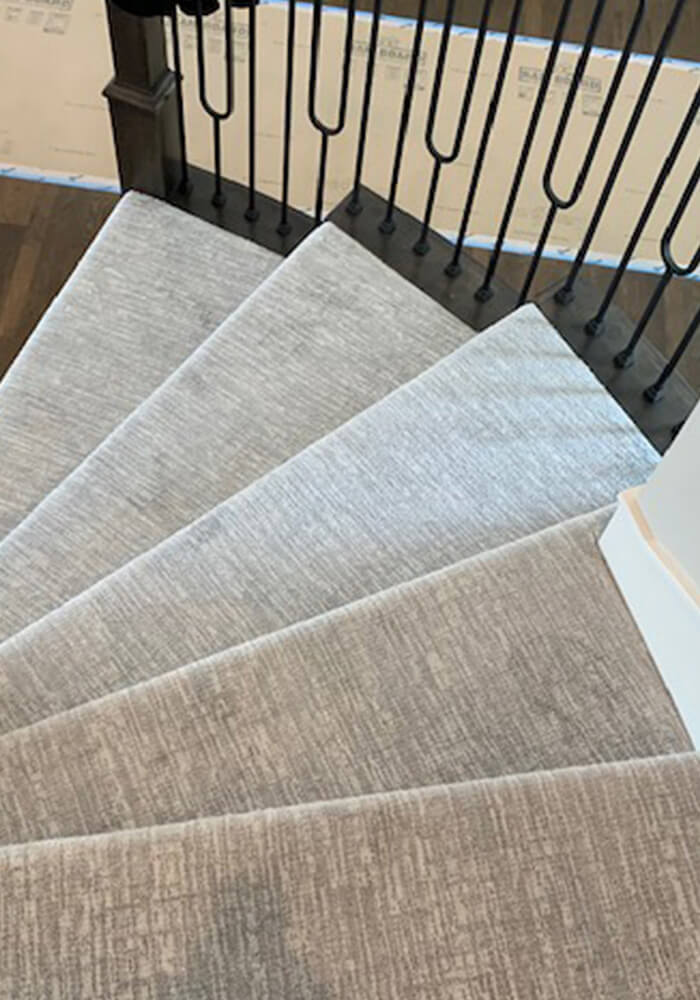 Spiral staircase with gray tone on tone patterned carpet installed by Big Bob's Flooring Outlet.