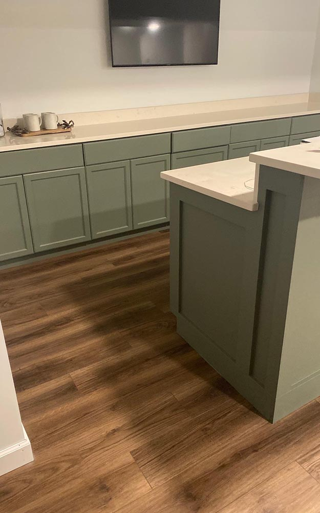 Wood look luxury vinyl plank installed with painted green cabinets